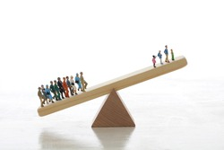 A diorama model that uses seesaws and balances to represent an aging society in which the population ratio of the elderly and young people changes