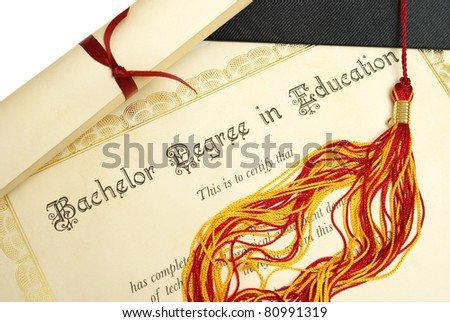 A diploma and grad hat represent a high achieving student in the field of education. - stock photo
