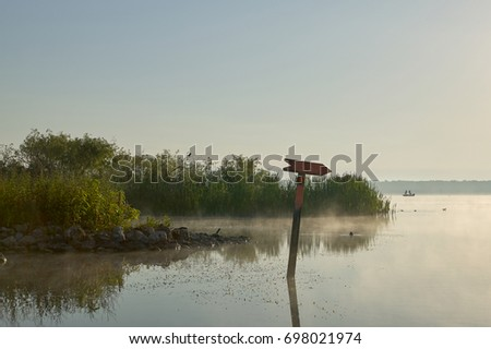 A directional lake channel marker on a beautiful, misty morning with clear blue sky at Lake Panasoffkee in Florida. #698021974