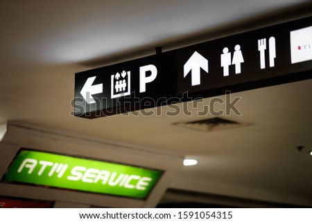 A directional signboard, indicating direction to an elevator, parking lot, toilet, food court, canteen, and atm