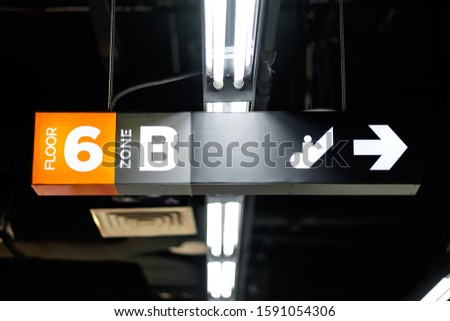 A directional signboard, indicating floor number, zone, elevator and toilet direction