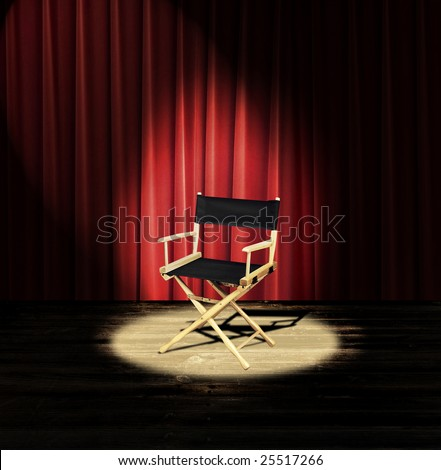 A directors chair on a stage with a red curtain and spotlight