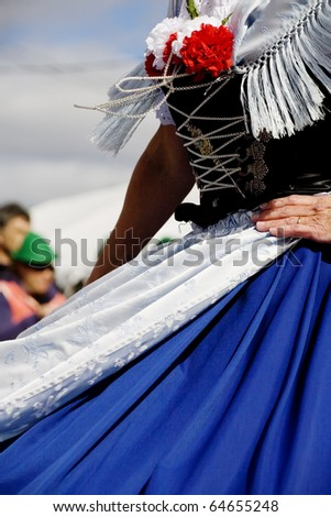 A dirndl dressed female dancer at Oktoberfest in mid turn with chains, skirt and apron flying.
