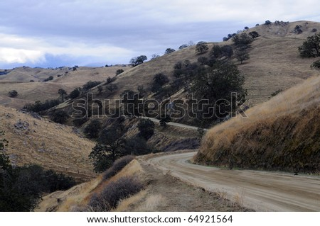 A dirt road snakes through the foothills of the Sierra Nevada Mountains, California