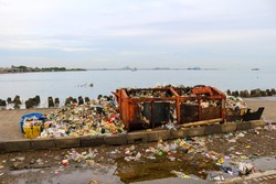 A dirty and full garbage near the sea. Bad view in a seashore.