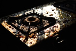 A Dirty and Grimy and Rusted Top of a Gas Stove with Food and oil Stains in a kitchen
