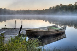 A dirty boat is parked by a wooden pier on a calm lake. It is dawn and soon the sun will be rising.