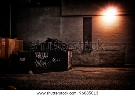 A dirty, dark, shadowy and dangerous looking urban back-alley at night time with garbage dumpster.
