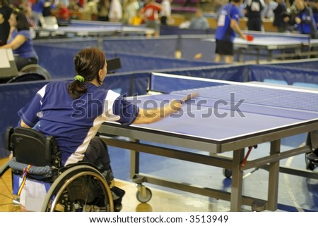 A disability female playing table tennis in an official competition.