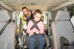A disabled child in a wheelchair being helped into a specially adapted van / Working with disability