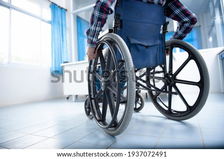 A disabled man on a wheelchair in the office Young man with disabilities in Asia. A man on a wheelchair Recovery and health care ideas Teamwork in Office Photo stock ©