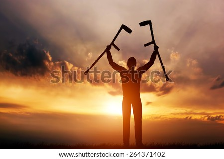 A disabled man raising his crutches at sunset. Positive concept of cure, recovery, medical miracle, hope, insurance etc.