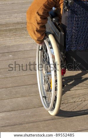 A disabled man sitting in a wheel chair with his hand at the wheel