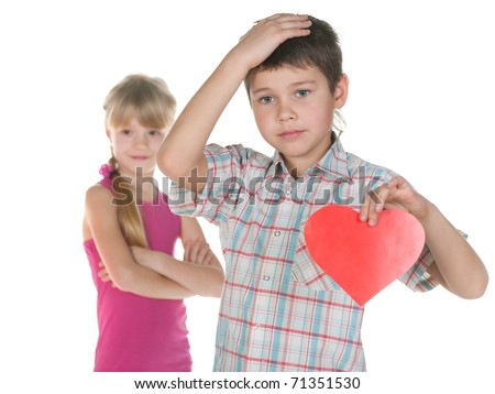 A disappointed boy is holding a red heart in his hand as his girl ignores him; isolated on the white background