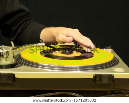a disc jockey while transmitting a track on a vinyl record in a disco