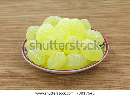 A dish filled with lemon drops on a wood surface.