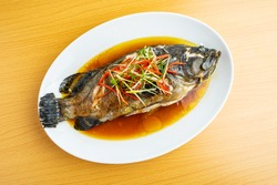 A dish of Cantonese steamed grouper on wooden table