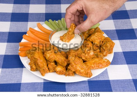 A dish of chicken hot wings, celery and carrots with dipping sauce attracts a man who dips a wing into some tasty ranch sauce at a picnic.