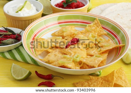 A dish of nachos covered in melted cheese and jalapeno peppers. With dishes of salsa and sour cream in the background. Garnished with lime and chilies. On a yellow background.