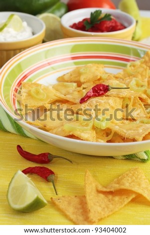 A dish of nachos covered in melted cheese and jalapeno peppers. With dishes of salsa and sour cream in the background. On a yellow background.