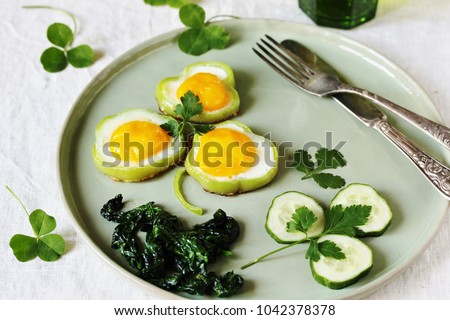 a dish on St. Patrick's Day. green breakfast. eggs in the form of clover. Fried Eggs Shamrock  in Green Pepper rings with Braised Spinach. parsley leaves like clover leaves.