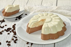 A dish with an appetizing mousse layer (vanilla and chocolate) cake on a wooden surface decorated with coffee beans and white linen lace napkin