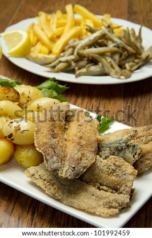 a dish with different fish fried and potatoes - stock photo