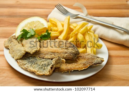 a dish with sardines fried and  potatoes