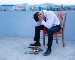 A disheartened man in a suit, broken-hearted after being rejected.