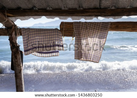a dishtowel hangs for drying in the sun on a wooden scaffolding with breaking waves  in the background