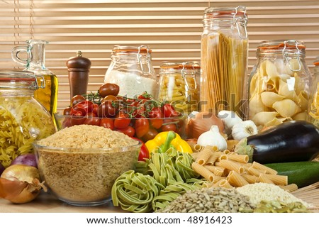 A display of healthy foods including various vegetables, jars of pasta, rice, seeds, onions, garlic, olive oil, aubergine, tomatoes, peppers, spaghetti and courgettes