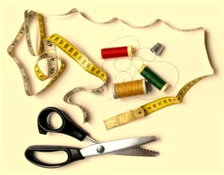 A display of items used for sewing.  The tape measure lies in a striking swirling pattern. The reels are a beautiful red, green and gold. The silvery thimble echoes the blades of the scissors