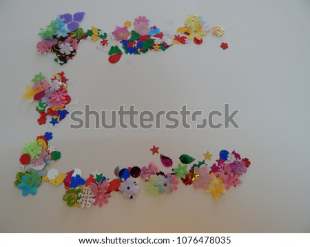 A display of multiple colored montage s of childrens craft pieces - leaves, stars, buttons, butterflies, flowers, and beady eyes, all laid out in various forms on a white background.