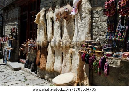 A display of traditional Azeri handicrafts souvenir hats, bags and sheepskin furs on the Main Street of Lahic, Lahij, a highland village in Azerbaijan of Caucasus mountain ranges.