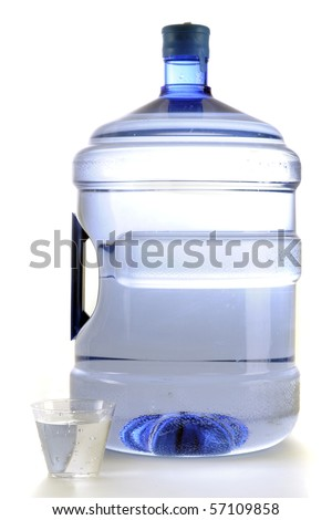 A disposable glass of water by a five-gallon jug of office water.