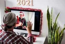 A distant couple on a video call from home for Christmas greetings. The man shows many gift packages while the woman raises her hand in greeting