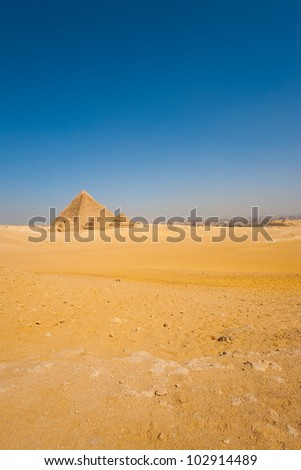 A distant view of the Giza pyramids in a vast and only desert backed by the city of Cairo, Egypt