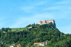 A distant view on the Riegersburg castle in Austria towering above the area. Clear blue sky above the castle. The massive fortress was build on the rock. Defensive structure from the middle ages. Calm