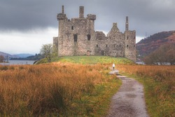 A distant young female tourist approaches the historic ruins of Kilchurn Castle  at Loch Awe in Argyll and Bute on a moody day in the Scottish Highlands, Scotland.