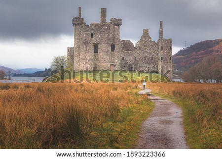 A distant young female tourist approaches the historic ruins of Kilchurn Castle  at Loch Awe in Argyll and Bute on a moody day in the Scottish Highlands, Scotland. Stock photo ©