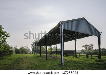 A disused farm building in Yorkshire, UK. It stands in a paddock surrounded by fences and gates. The metal structure backlit having been photographed contre-jour.