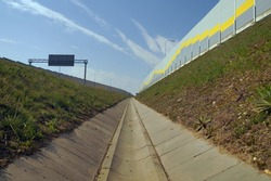 A ditch draining the highway. Wall from sound absorbing panels.