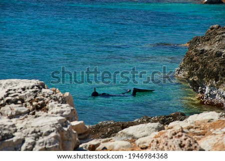 a diver dives in front of the rocks in a clear crystalline sea at Fontane bianchi seaside resort near Syracuse, Sicily Foto stock ©