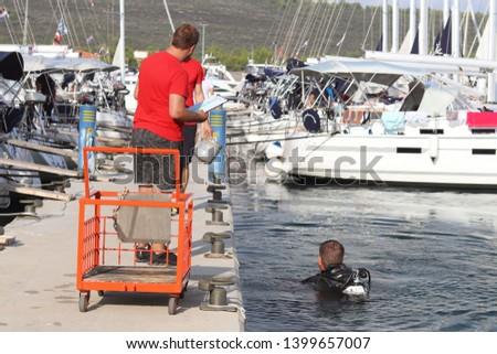 A diver scuba dives in the marina near the pier with sailing yachts. Check for damage below the ship's waterline after the voyage. Sabbath reception rented boats. Inspectors of the charter company.