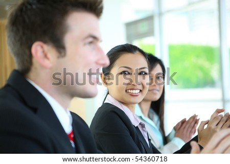 A diverse attractive man and woman business team  clapping at meeting