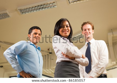 A diverse business team stands and looks confidently at the camera which is at a low angle