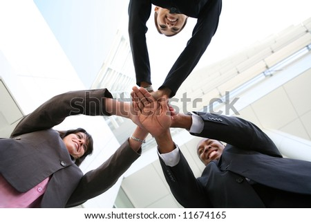 A diverse business team with hands together at company