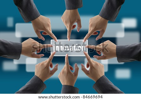 A diverse business team with hands together push Innovation button for brainstorm concept
