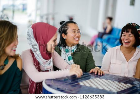 A diverse group of Asian women friends sit around a table to talk, gossip and chat. They are from multiple ethnicities and are smiling and laughing as they converse in a relaxed, easy and light way. #1126635383