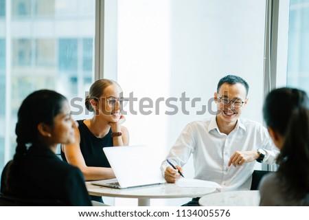 A diverse team of business people have a productive and efficient meeting. They are sitting around each other at a table and having an animated discussion. Some of them are smiling while others think.
